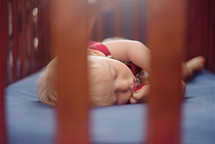 a toddler sleeping in a crib