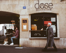 a man walking on a city street in front of a cafe
