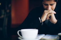 coffee mug and Bible resting on a table in front of a man in prayer