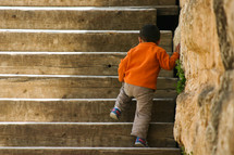 a toddler boy walking up steps outdoors