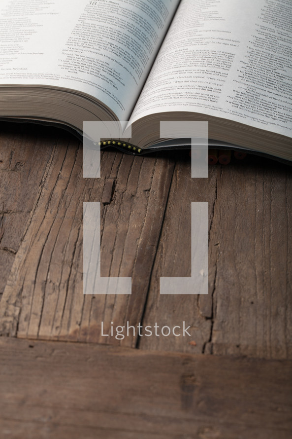 An open book on a wooden surface.