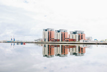 reflection of buildings on water in a marina