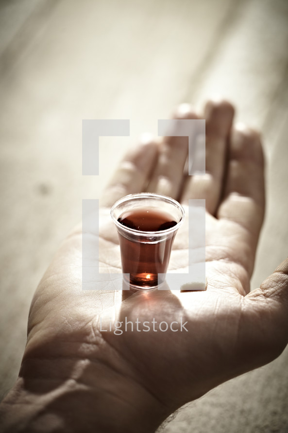 A Communion cup and wafer in the palm of a hand.
