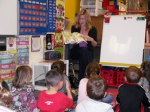 A teacher reading a story book to her kindergarten classroom