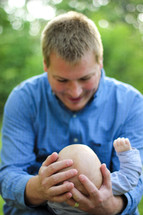 Man cradling his infant son outside.