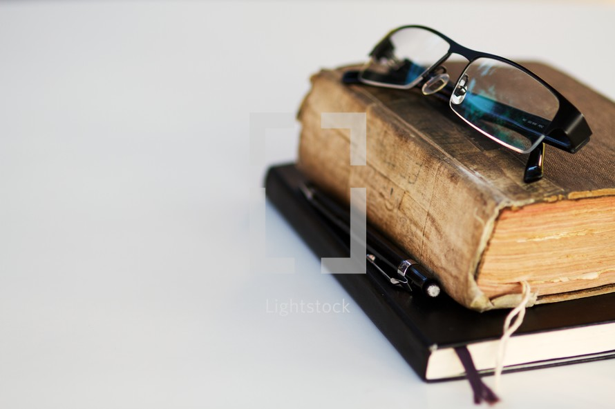 A pair of reading glasses rest on a Bible and journal - isolated on white