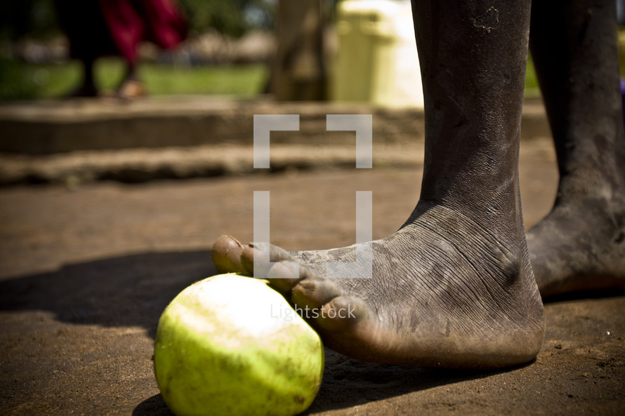 An apple rests under a dirty foot.