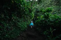 a woman hiking through the jungle