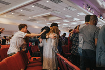 placing hands on others in prayer at a worship service