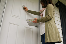 a woman with a pan of food knocking on a door
