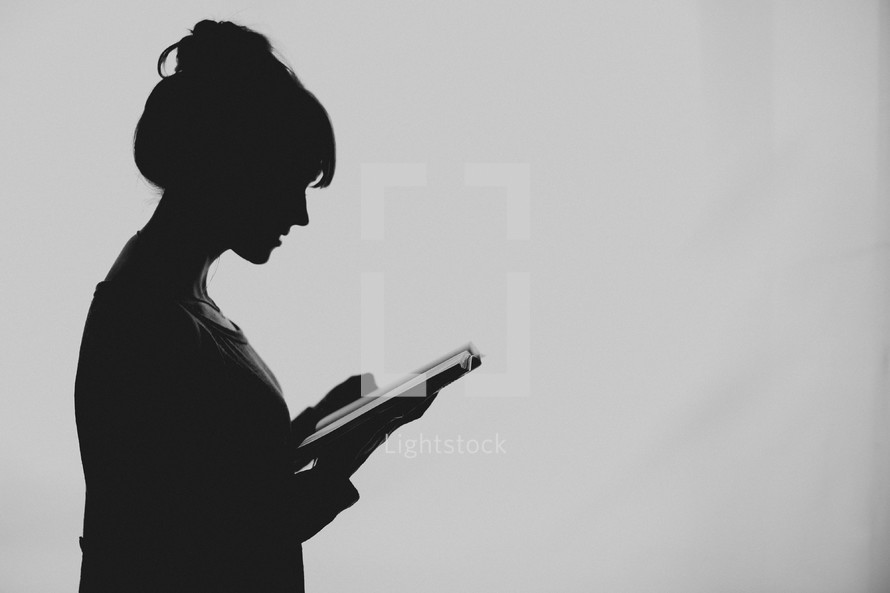 A young woman silhouetted reading her Bible