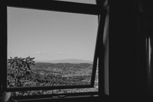 view of rolling hills out a window in Italy