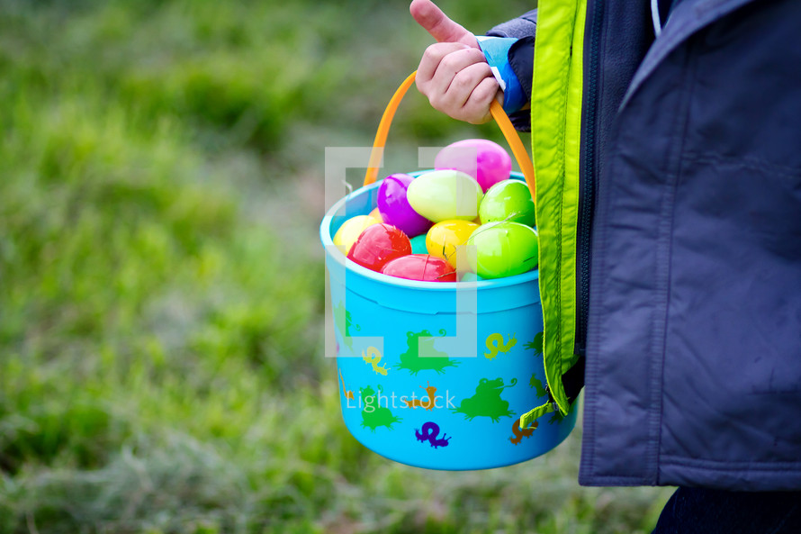 A child holding a basket of colorful Easter eggs.