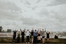 people standing on a rooftop with hands raised