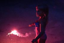 little girl holding a sparkler on a beach