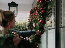 A woman decorates her house with a Christmas garland.