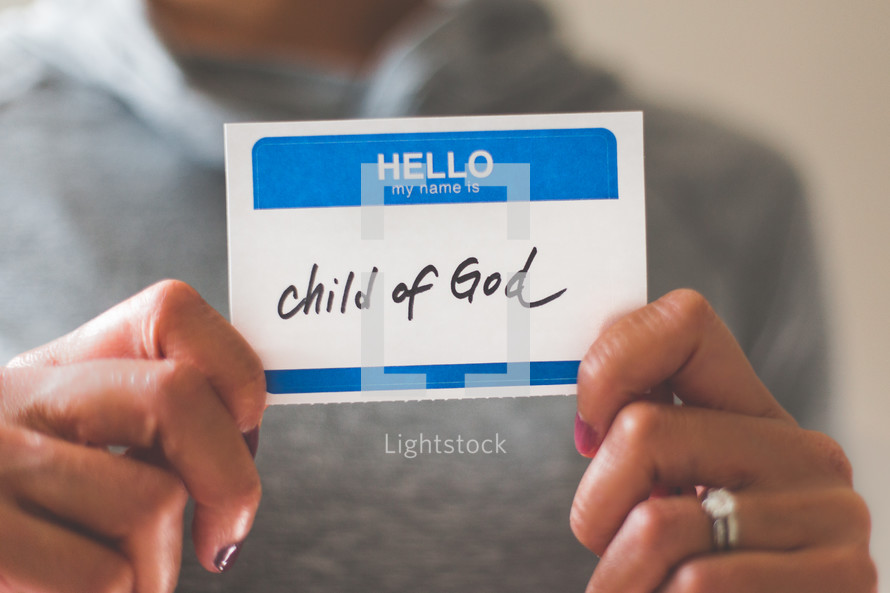 woman holding a name tag with the word child of God