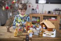 a child playing with a toy nativity scene