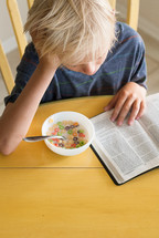 morning devotional, boy child reading a Bible while eating milk and cereal