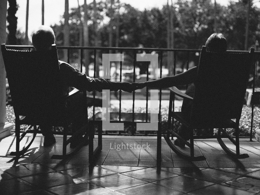 couple in rocking chairs holding hands on a porch