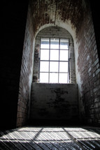 A narrow arched brick room with  a window through which the sun is shining.
