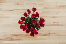 Red roses on a wooden table from above.