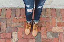 legs of a woman in ripped jeans and boots