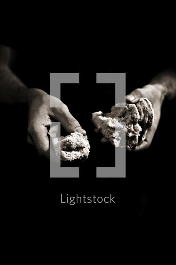 Hands holding broken bread