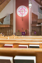 hymnals in church pews and organ pipes
