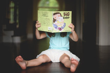 a girl child reading a big sister book