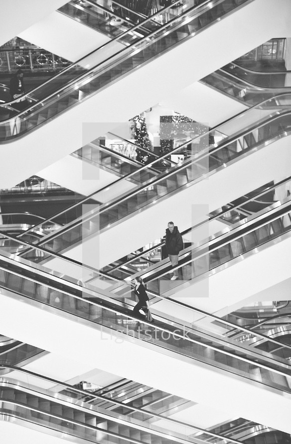 People riding up and down escalators at a mall