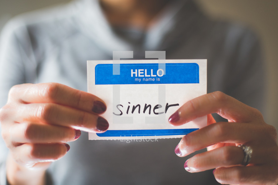 man holding a name tag with the word sinner