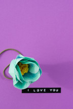 """I love you,"" with a turquoise flower on a purple background."