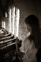 a girl praying in a church