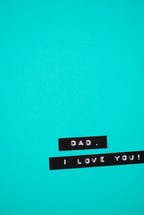 "A label reading, ""Dad, I love you,"" on a turquoise background."