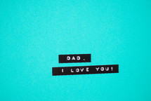 """Dad, I love you,"" on a blue background."