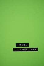 "A label reading, ""Dad, I love you,"" on a green background."