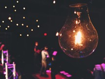 single lightbulb hanging over a band on stage