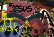 graffiti covered wall with word Jesus