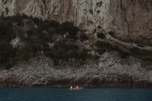 padding a boat along a shoreline in Italy