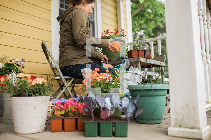 a woman on a porch planting flowers