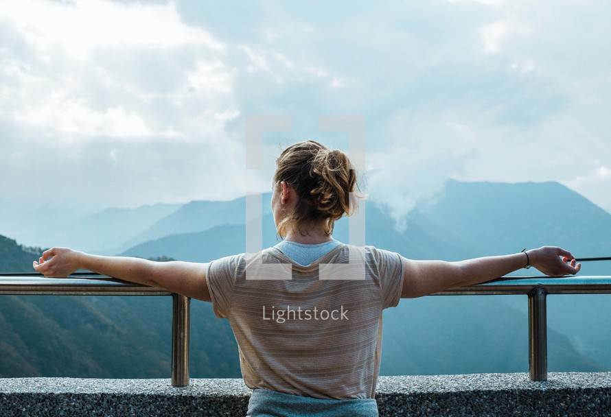 woman looking at mountains over a railing