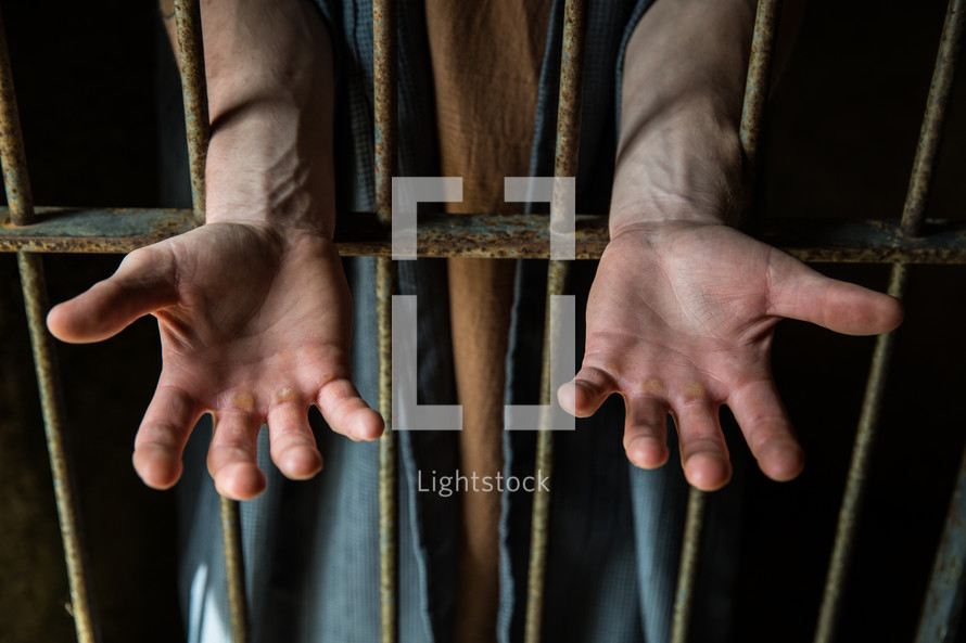 Hands held outstretched through prison bars.