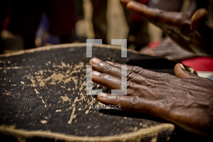 Black hands playing on a drum - music