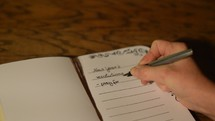 woman writing her New Year's resolutions down