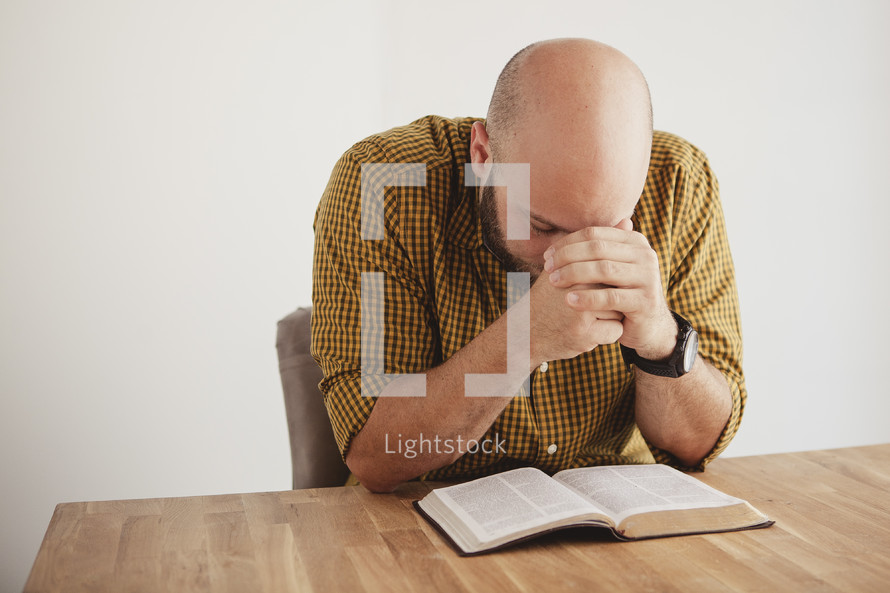 man with her head bowed in prayer over a BIble