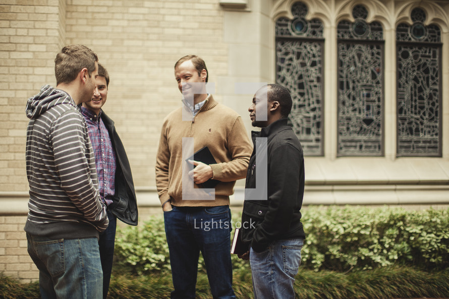 group of men standing in front of a church before a Bible study