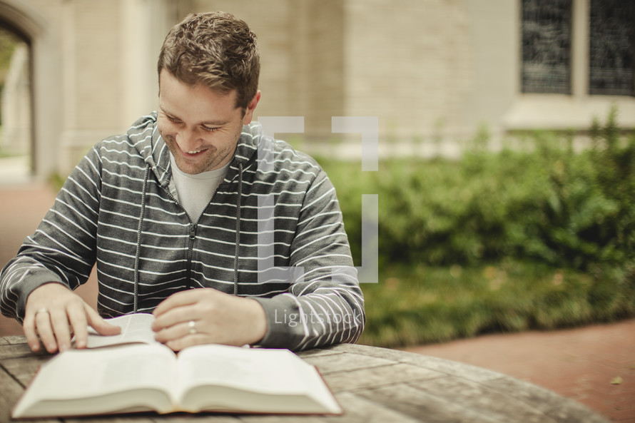 man writing in a journal from an open Bible