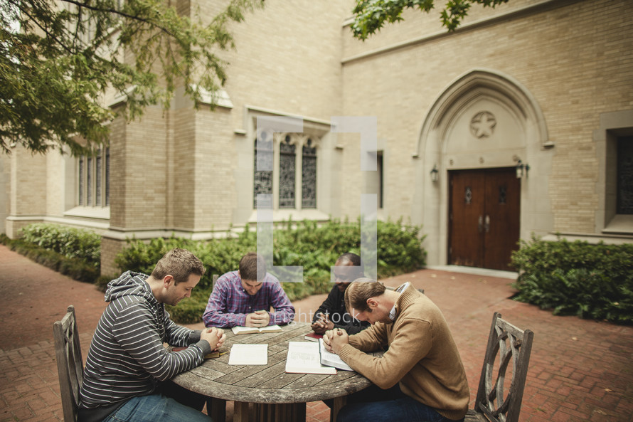 Men's BIble study group praying at table