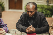 Men at bible study in prayer